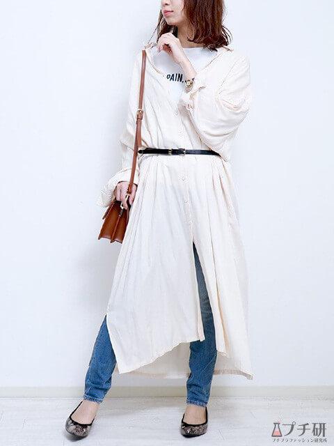 白のシャツワンピースにブルーデニムのスリムパンツをレイヤードしたナチュラルコーデの画像